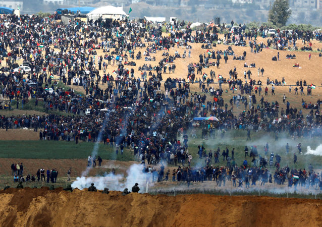 Militares israelenses usam gás lacrimogêneo contra os manifestantes palestinos na Faixa de Gaza, em 30 de março de 2018