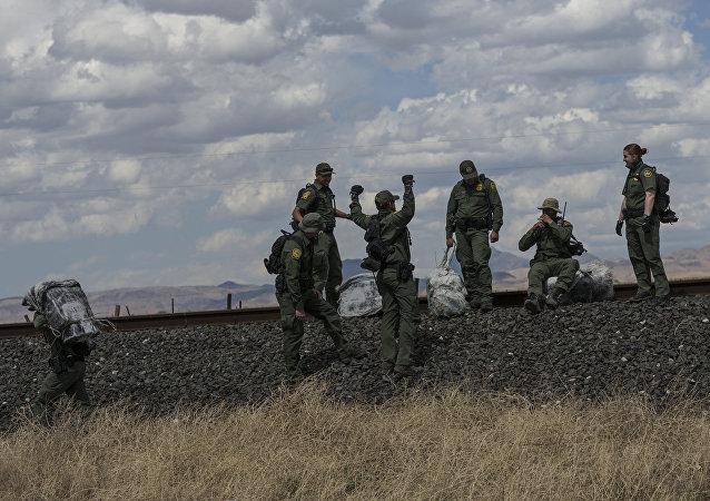 Agentes de patrulhamento fronteiriço norte-americanos com fardos de maconha na fronteira entre México e EUA