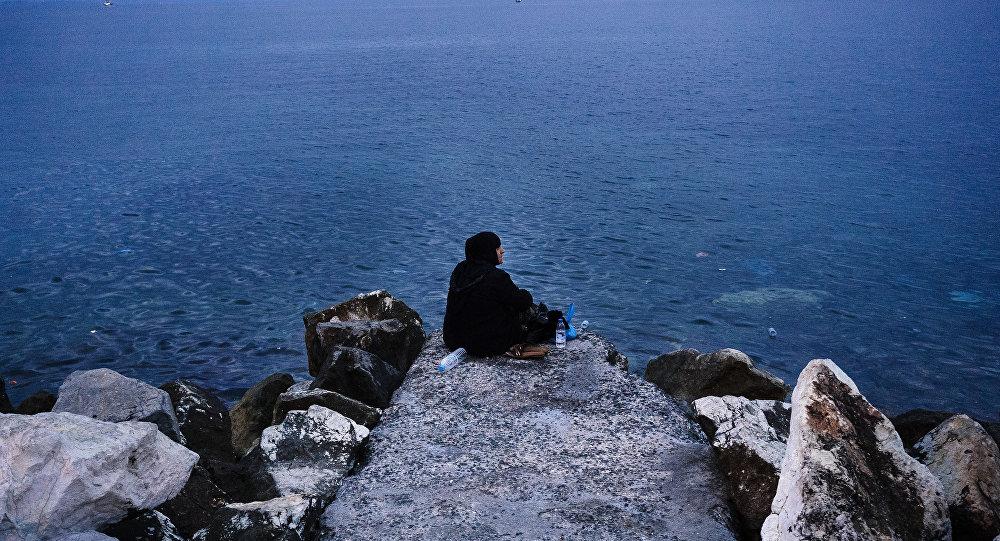 Mulher idosa sentada no quebra-mar do porto de Mytilene, Grécia