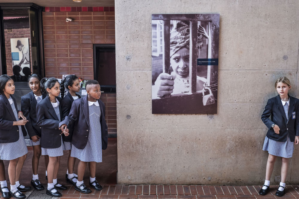 Alunas sul-africanas perto de um cartaz que retrata a ex-mulher de Nelson Mandela