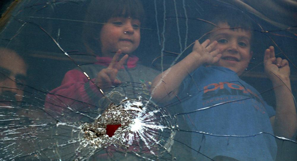 Crianças olham pela janela de um ônibus perto da cidade de Al-Bab, norte da Síria, depois que os combatentes e suas famílias foram retirados da cidade de Douma, 3 de abril de 2018