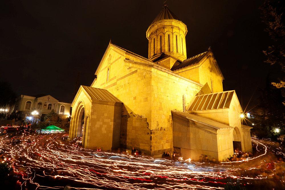 Crentes andam perto da Catedral de Sioni com velas acesas após a missa pascal, em Tbilisi, na Geórgia