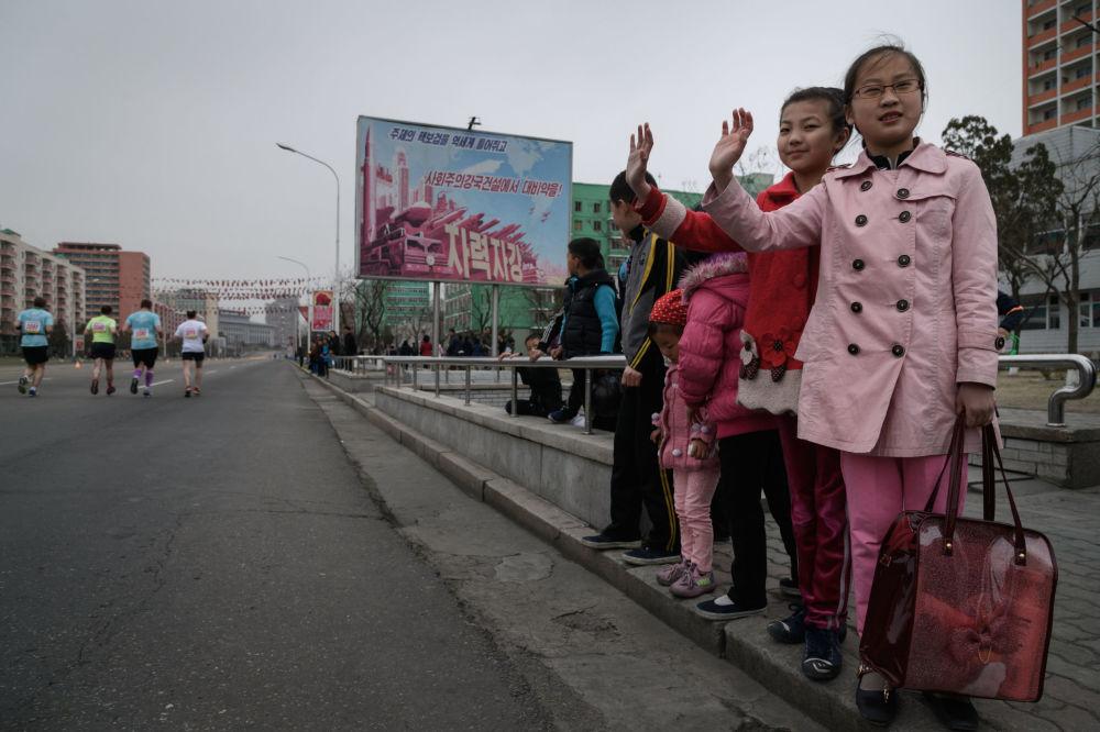 Crianças saúdam participantes da maratona anual em Pyongyang, 8 de abril de 2018