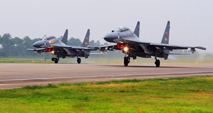 Dois caças chineses SU-30 decolam de um local não especificado para fazer uma patrulha sobre o Mar do Sul da China.