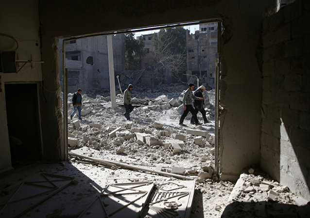 As pessoas andam em uma área atingida por ataques aéreos no bairro rebelde de Douma sitiada de Damasco, na Síria. (Arquivo)