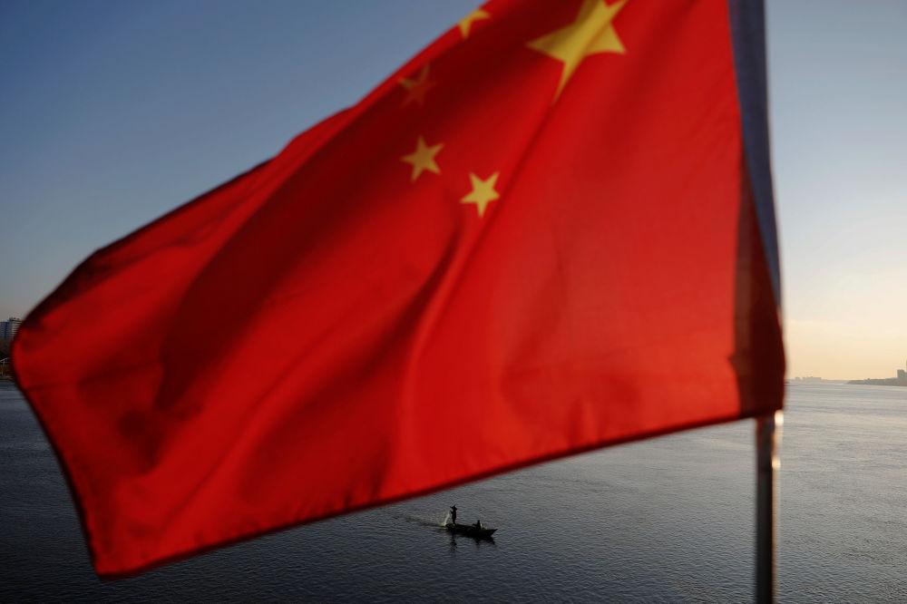 Pescador norte-coreano, com a bandeira chinesa em primeiro plano, no rio fronteiriço Yalu, entre a Coreia do Norte e a China
