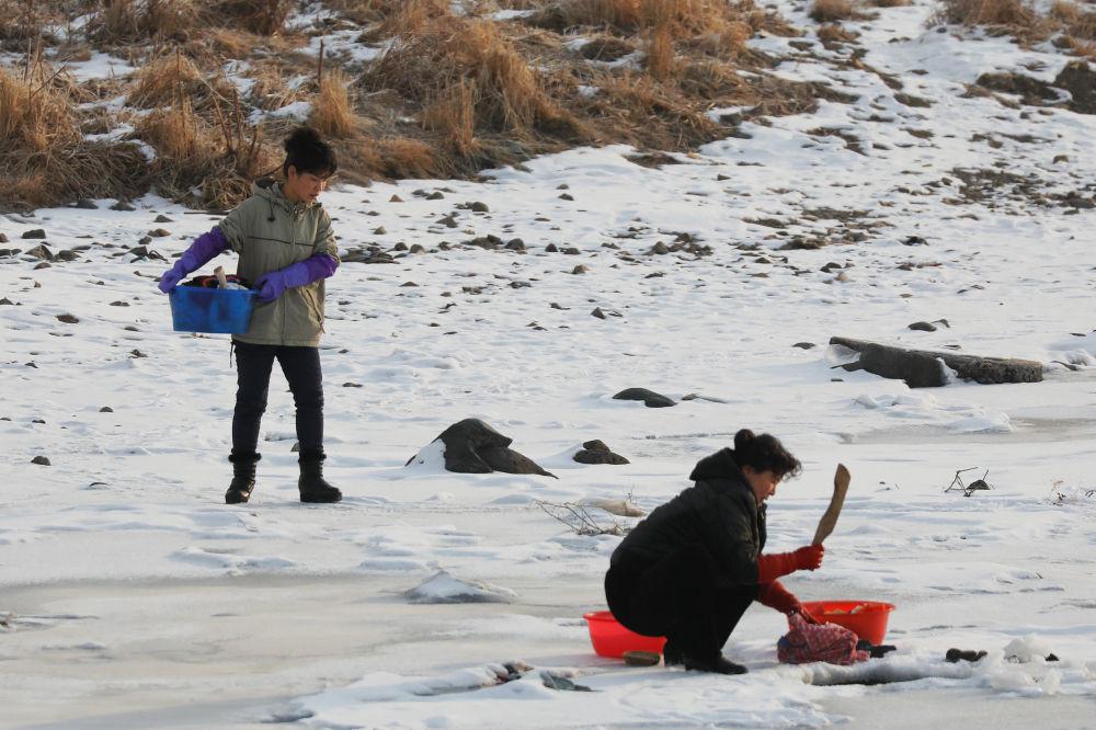 Norte-coreanos captados no rio gelado Yalu a partir da parte chinesa da fronteira
