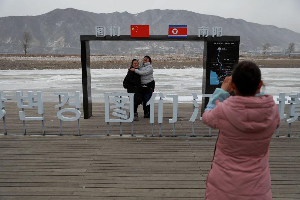 Pessoas se fotografam perto da fronteira com a Coreia do Norte, na China