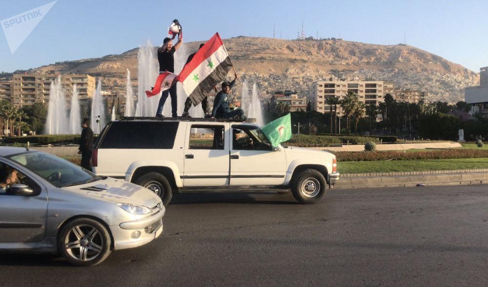 Sírios durante uma manifestação contra os ataques aéreos da coalizão liderada pelos EUA em uma das ruas de Damasco