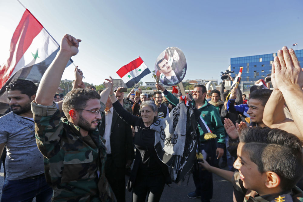 Cidadãos sírios com retratos do presidente Bashar Assad e com bandeiras da Síria durante uma manifestação contra os ataques aéreos da coalizão liderada pelos EUA