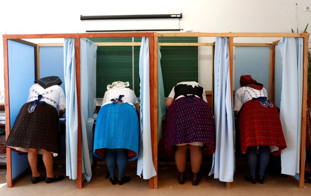 Mulheres húngaras de trajes tradicionais preenchem as cédulas eleitorais durante as legislativas