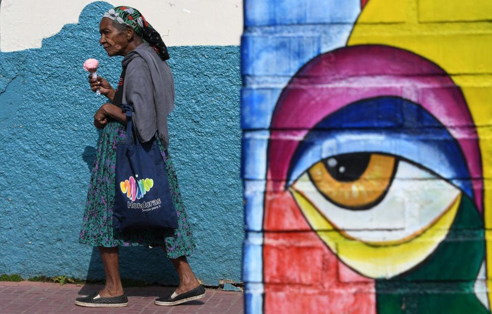Mulher come sorvete caminhando por uma das ruas da capital hondurenha, Tegucigalpa