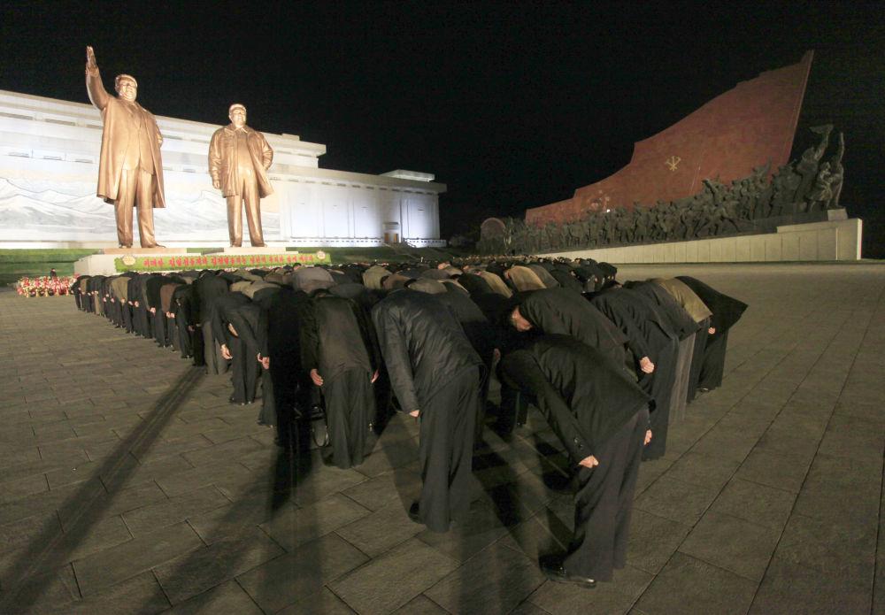Norte-coreanos fazem reverência aos monumentos dos líderes norte-coreanos Kim Il-sung e Kim Jong-il, Pyongyang, 15 de abril de 2018