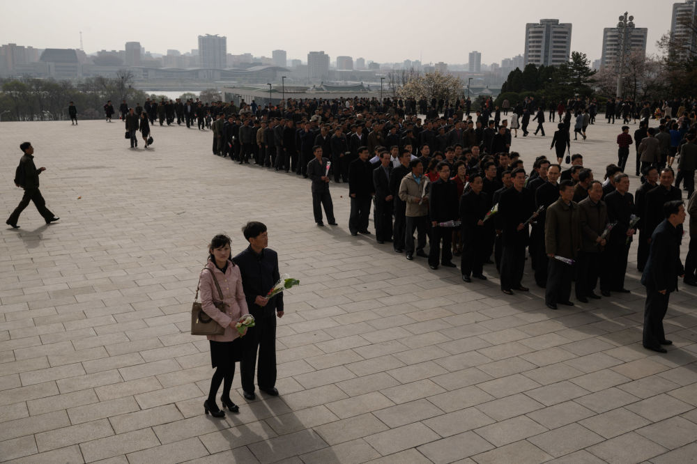 Pessoas depõem flores nos monumentos dos líderes norte-coreanos Kim Il-sung e Kim Jong-il, Pyongyang, 15 de abril de 2018