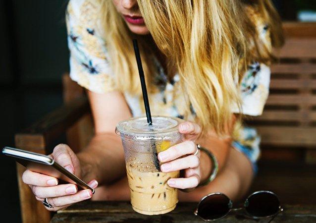 Uma loira com celular e bebida (imagem referencial)
