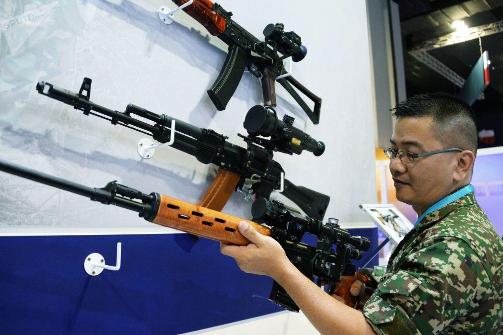 Visitante da exposição na Malásia observando armas de fogo de produção bielorrussa