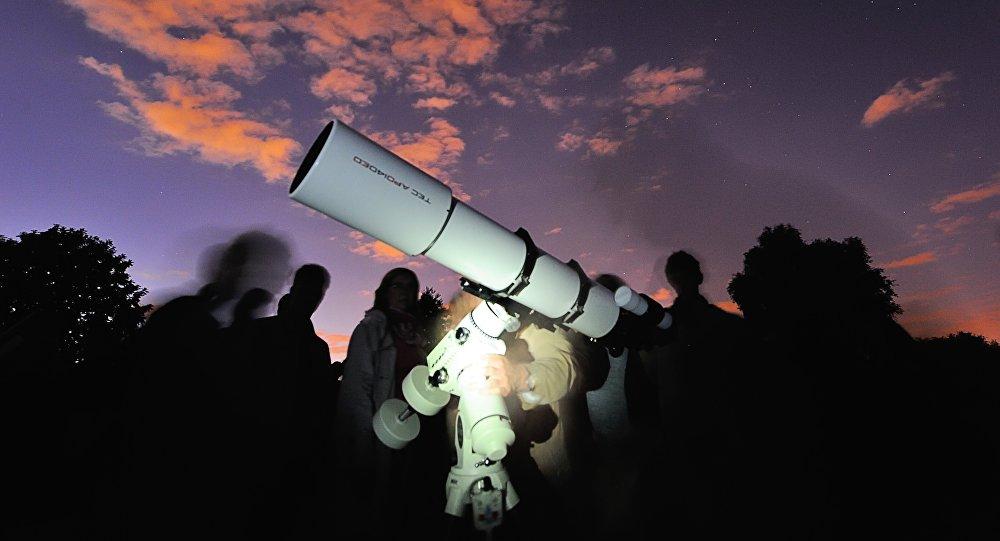 Pessoas observam estrelas através de um telescópio na cidade de Villeneuve-d'Ascq, França, 9 de agosto de 2013