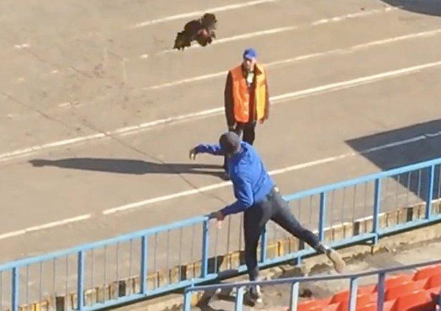 Torcedor atira um galo dentro de campo durante uma partida entre o Luch-Energiya Vladivostok e o FC Fakel Voronezh.