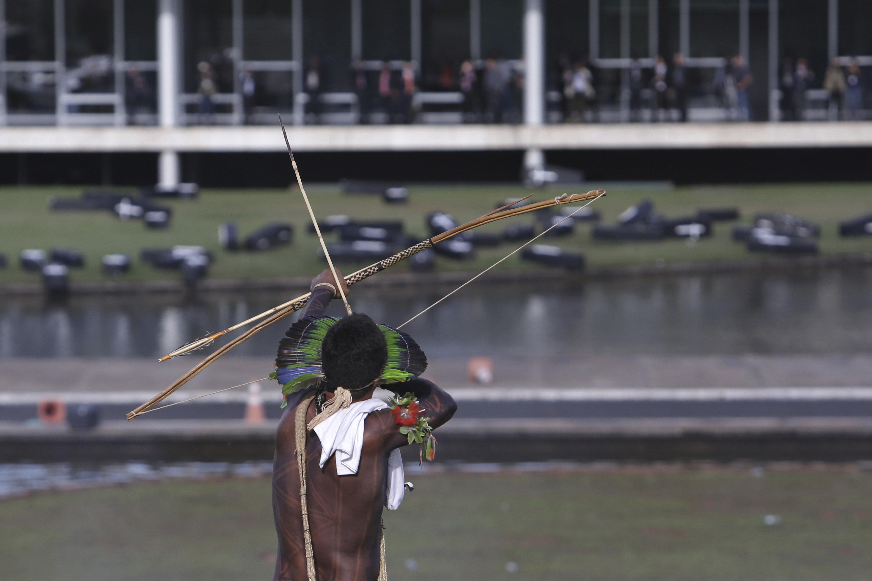 Um indígena mira seu arco no ar durante protesto em frente ao Congresso Nacional.