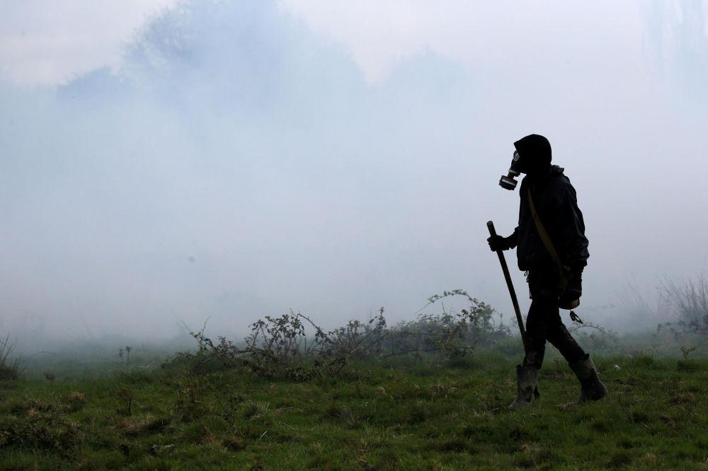 Manifestante atravessando um campo através de gás lacrimogêneo durante confrontos com policiais franceses em Notre-Dame-des-Landes, França.
