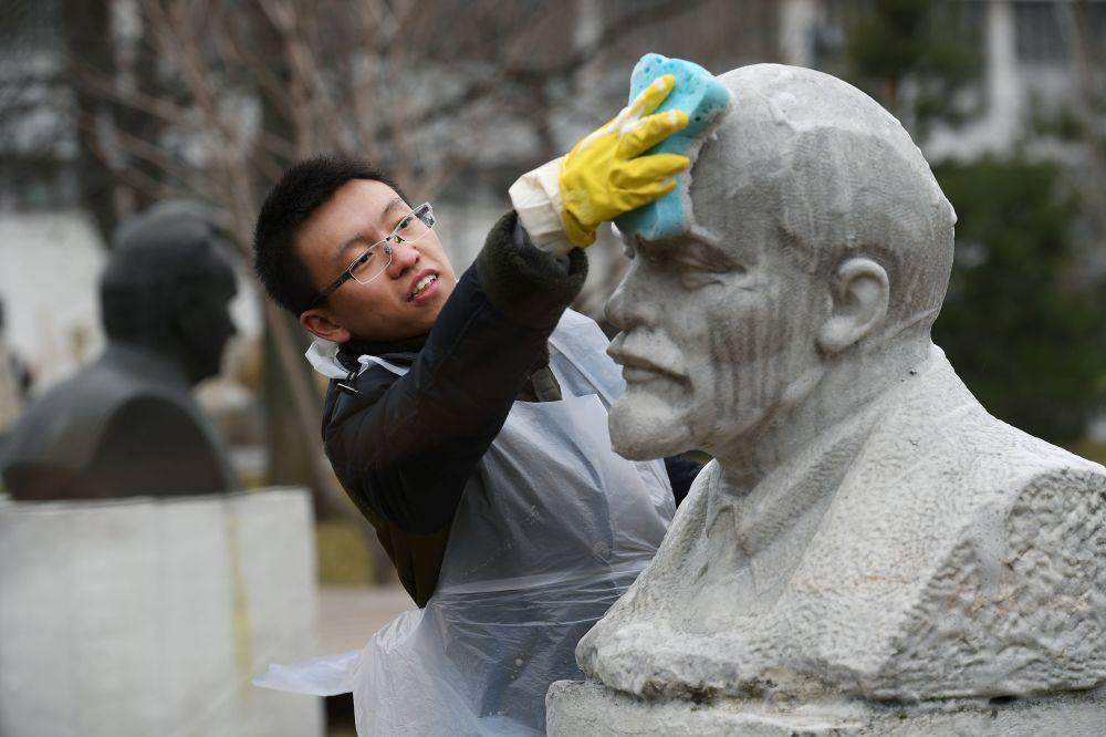 Um voluntário lavando o monumento a Lenin em Moscou