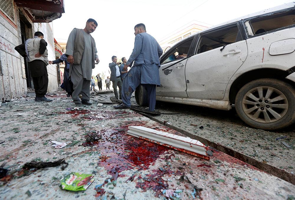 Homens afegãos inspecionam o local de uma explosão suicida em Cabul.