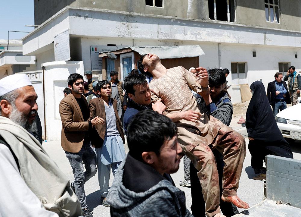 Parentes das vítimas levam um homem ferido para fora de um hospital após um ataque suicida em Cabul.