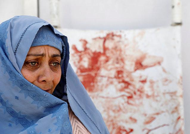 Uma mulher chora em um hospital após  ataque suicida em Cabul.