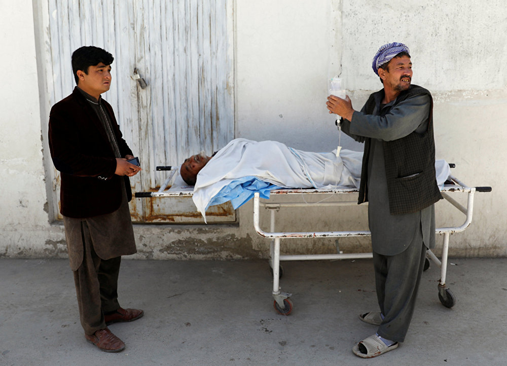 Um homem em meio a cadáveres de um hospital depois de um ataque suicida em Cabul, no Afeganistão.