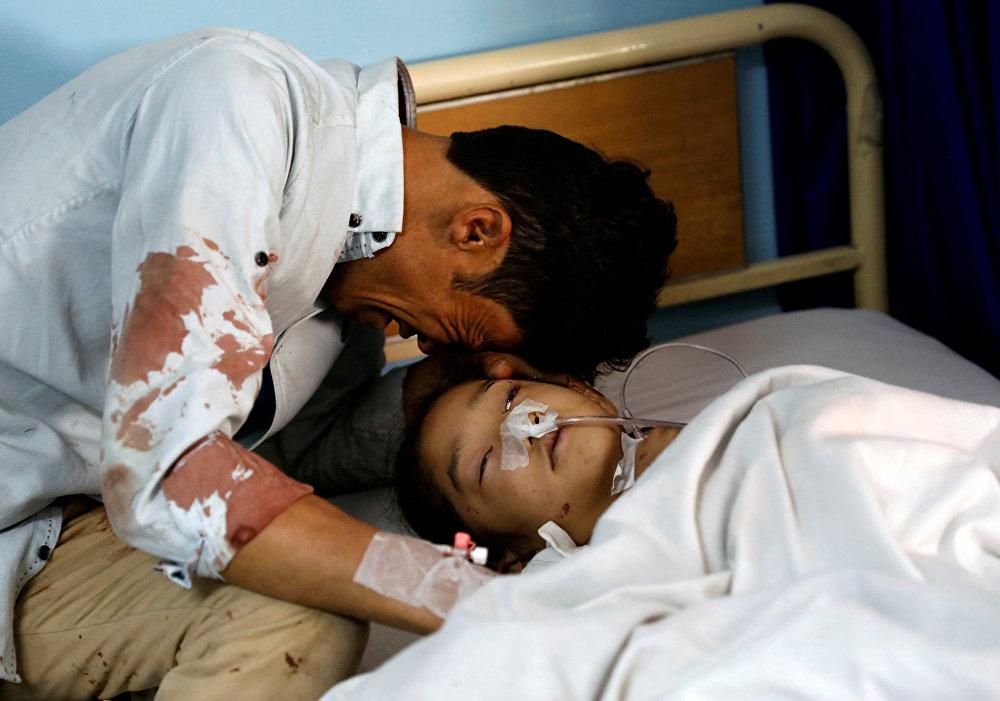 Um homem chora ao lado de uma menina ferida em um hospital depois de um ataque suicida em Cabul, no Afeganistão.