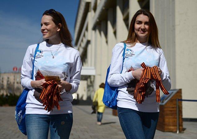 Voluntárias distribuindo fitas de São Jorge em Moscou no âmbito da iniciativa tradicional dedicada ao Dia da Vitória