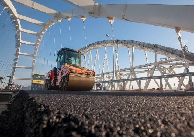 Veículos asfaltando parte rodoviária da ponte da Crimeia