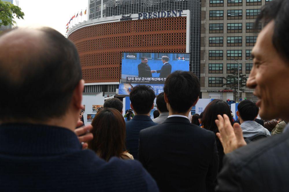 Pessoas em Seul aplaudem observando a transmissão do encontro histórico entre seus líderes ao apertarem as mãos na zona desmilitarizada que separa as duas Coreias