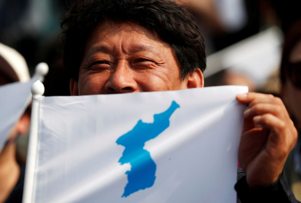 Homem mostra a bandeira do Império Coreano na véspera da cerimônia do encontro dos líderes da Coreia do Norte, Kim Jong-un, e da Coreia do Sul, Moon Jae-in