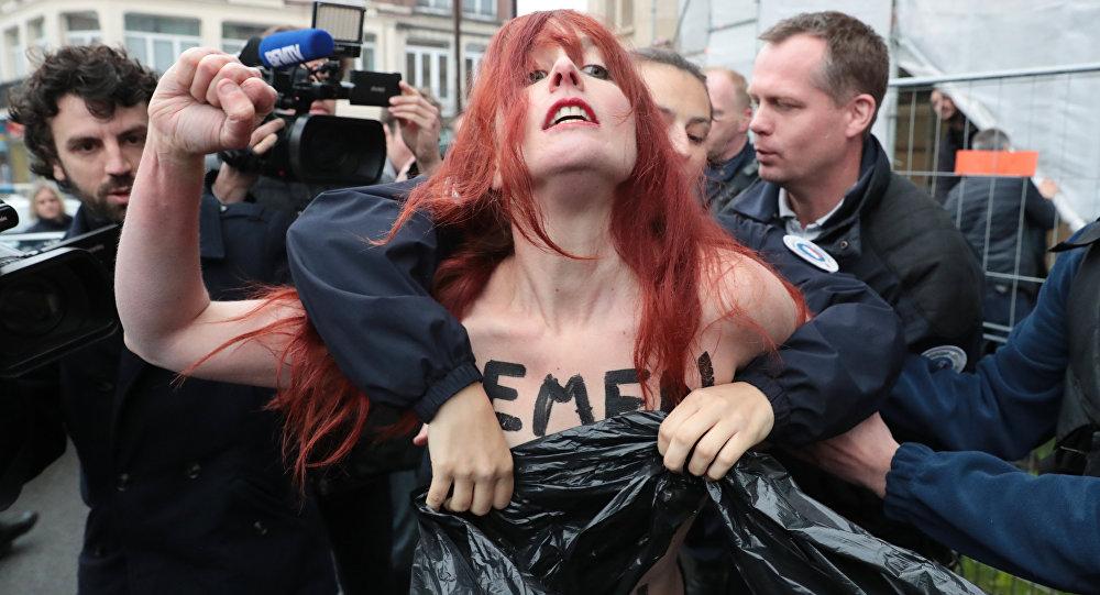 Polícia encobre os seios da mulher ativista do grupo Femen, durante os protestos contra a ex-candidata à presidência da França, Marine Le Pen, em Paris (foto de arquivo)