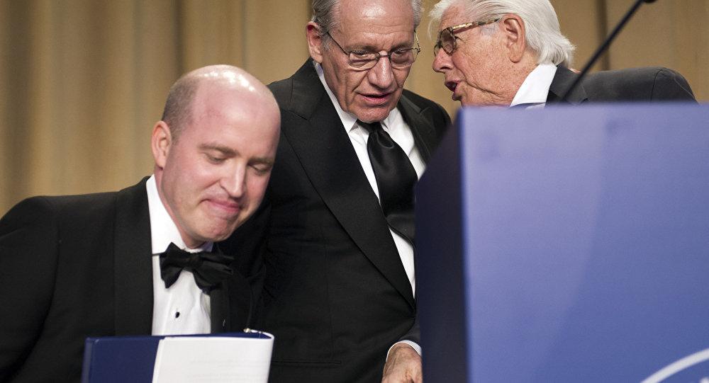 O presidente dos Correspondentes da Casa Branca, Jeff Mason, correspondente da Casa Branca à Reuters, senta-se em sua cadeira enquanto os jornalistas Bob Woodward e Carl Bernstein conversam durante o jantar da associação em Washington.
