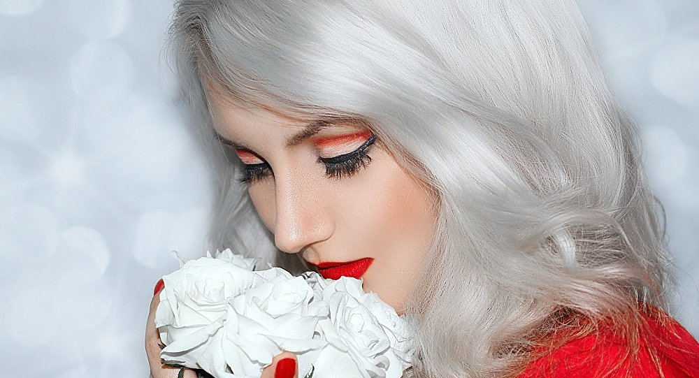 Mulher loira com flores (imagem referencial)