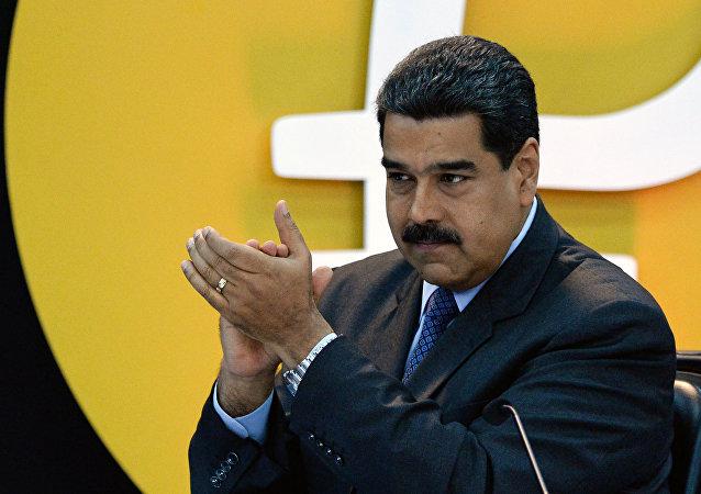 Nicolás Maduro, presidente da Venezuela, junto ao logo da criptomoeda petro
