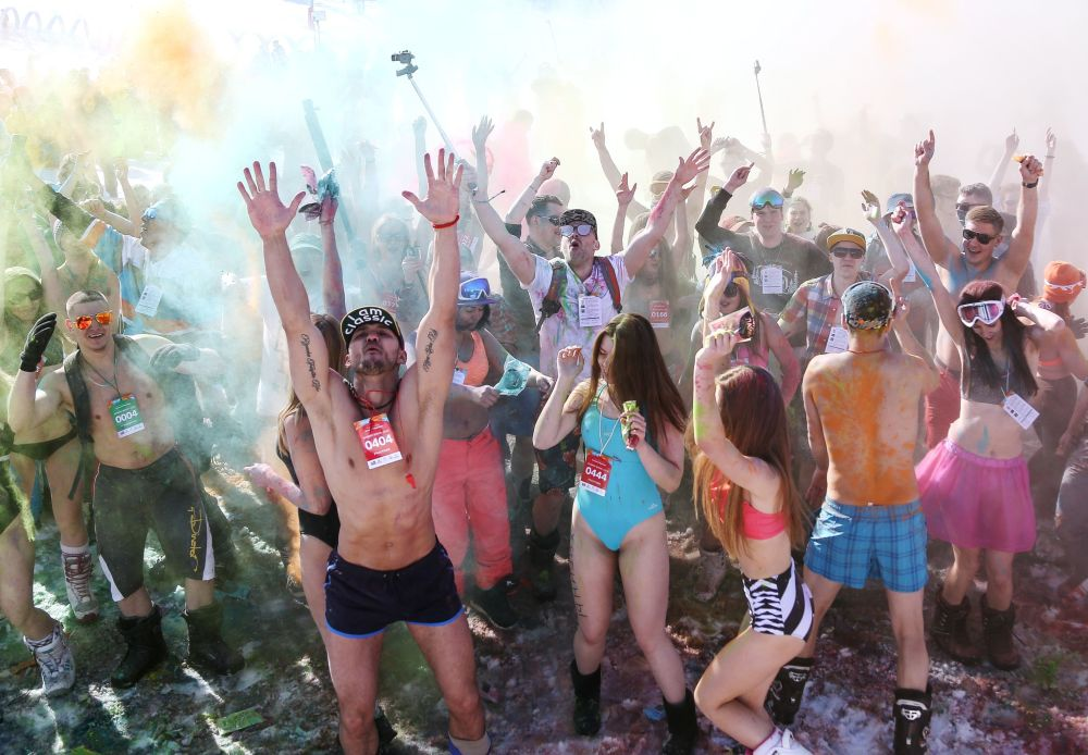 Participantes do festival celebram festa de biquíni usando tintas coloridas