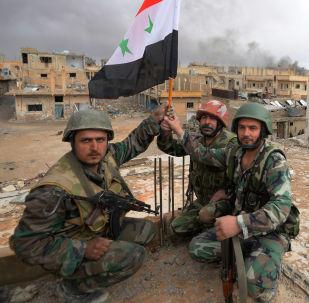 Soldados do Exército sírio com bandeira da Síria se alegram com a libertação de Palmira (foto de arquivo)
