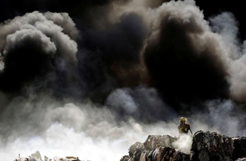 Bombeiro combate o fogo no centro de reciclagem de pneus vencidos, no México