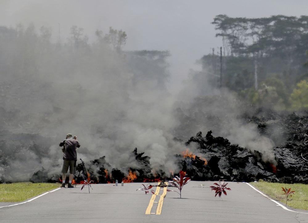 Pessoa não identificada tira foto de uma estrada sendo engolida por lava, no Havaí