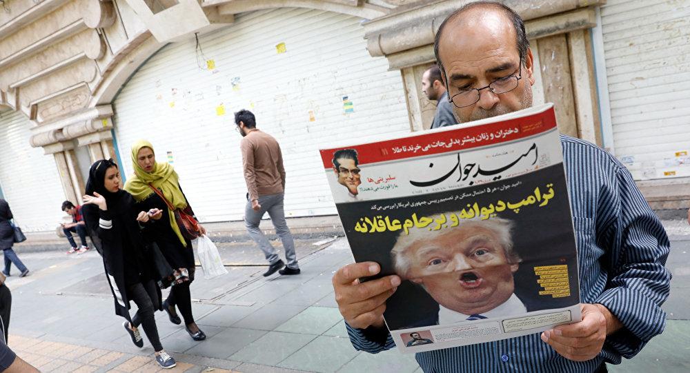 Iraniano lê jornal Omid Javan com foto do presidente dos EUA, Donald Trump, com uma manchete escrita em persa Trump louco e lógica do JCPOA (Plano de Ação Conjunto Global), 14 de outubro de 2017