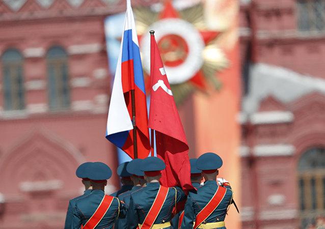 Militares do Batalhão da Guarda de Honra entram na Praça Vermelha com a bandeira nacional da Federação da Rússia e o estandarte da vitória, 9 de maio de 2018