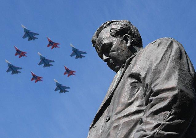 Caças Su-30SM do grupo de acrobacia aérea Russkie Vityazi e MiG-29 do grupo de acrobacia aérea Strizhi com o monumento ao escritor Aleksandr Tvardovsky em primeiro plano