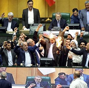 Deputados iranianos queimam dois papéis, um dos quais representa a bandeira norte-americana, e o outro - o acordo nuclear