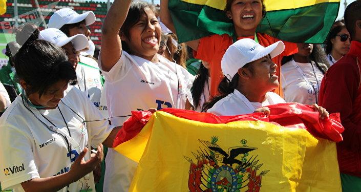 Equipe feminina boliviana na Street Child World Cup 2018 segurando uma bandeira do seu país