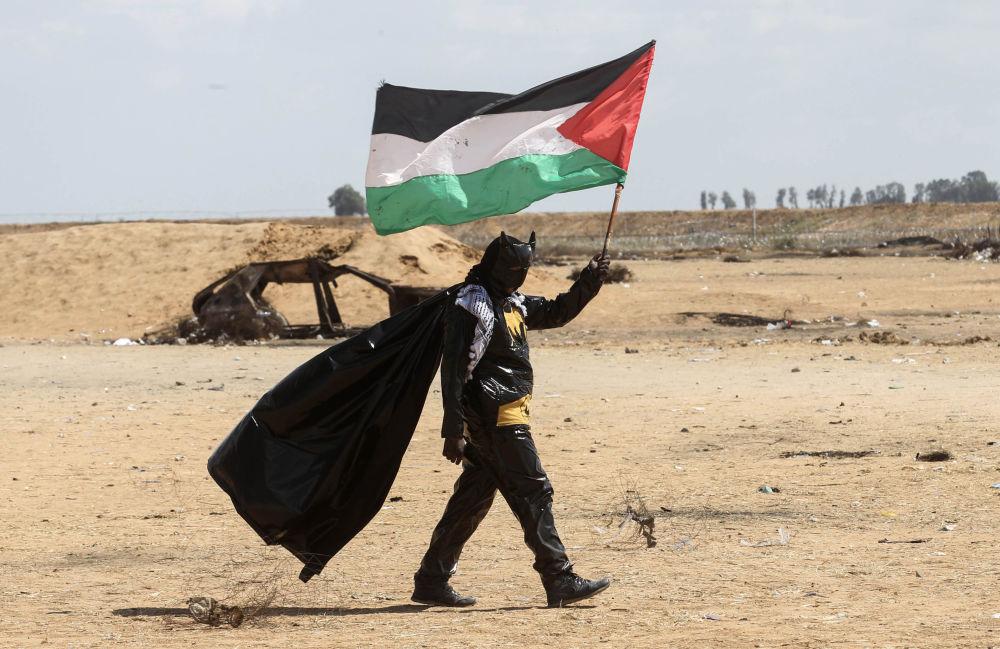 Manifestante palestino vestido de Batman segura a bandeira nacional perto da fronteira entre Israel e Faixa de Gaza