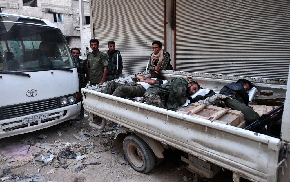 Soldados do exército sírio descansando antes da batalha na área do antigo campo de refugiados palestinos Yarmouk no subúrbio a sul de Damasco