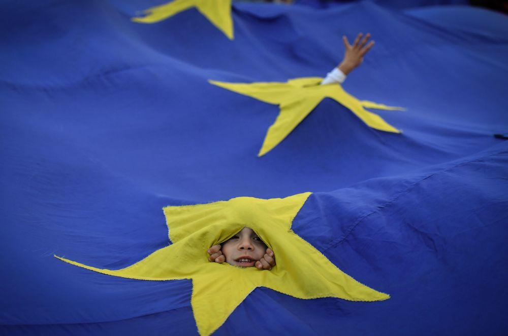 Garoto e bandeira da União Europeia, durante uma manifestação a favor do afastamento do premiê romeno, em Bucareste